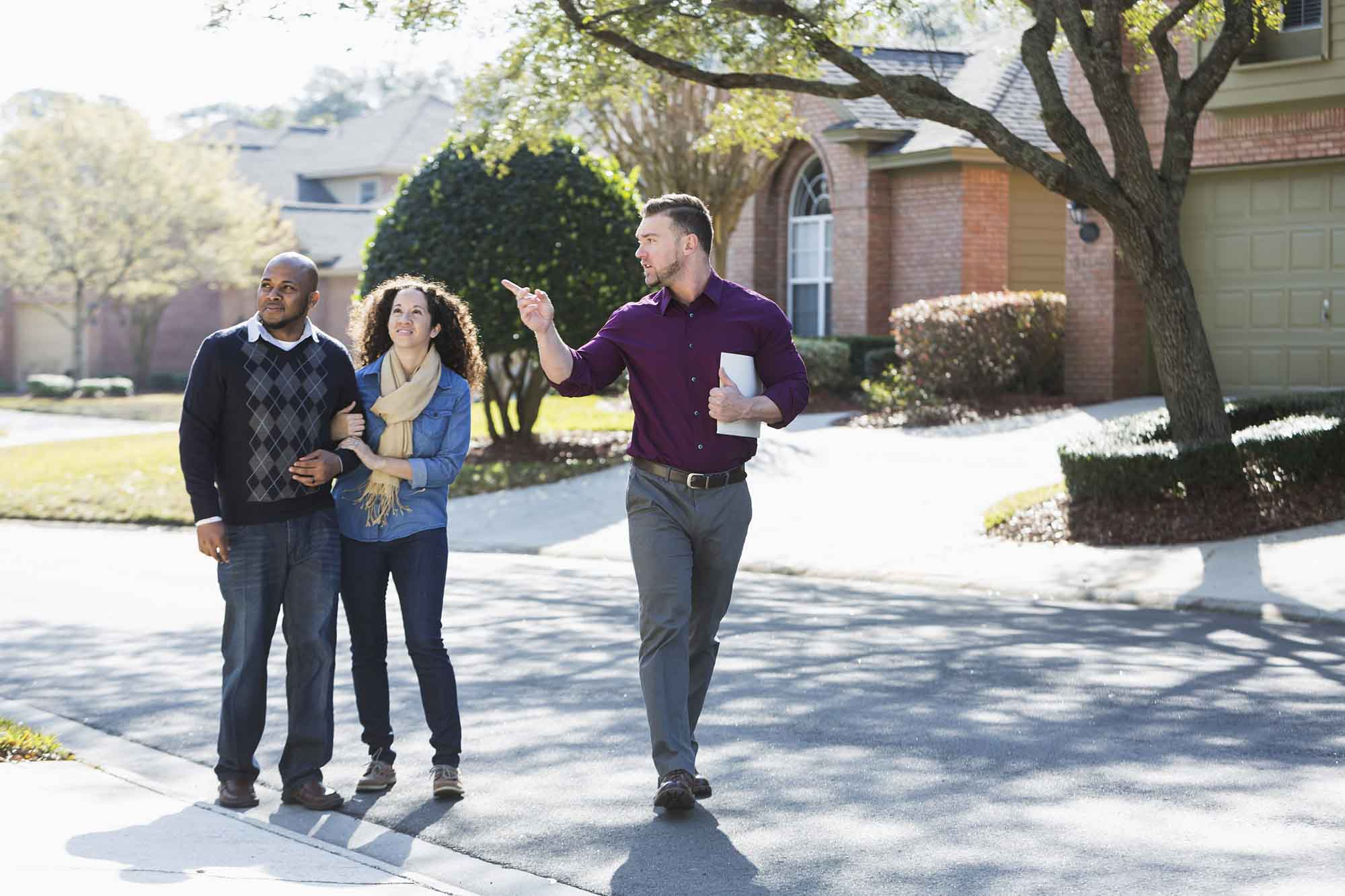 An African American couple walking on a residential street, with a young man holding a folder.  He is a real estate agent, pointing at a house, talking.