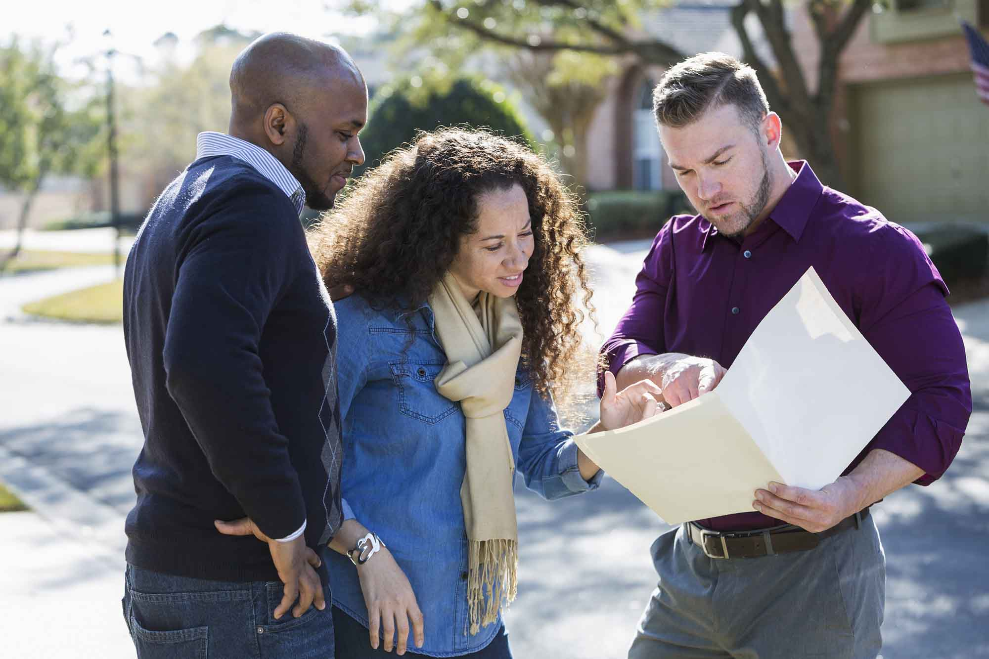 An African American couple standing outdoors on a sunny day on a residential street, with a young man holding a folder.  He is a real estate agent, or maybe a contractor.