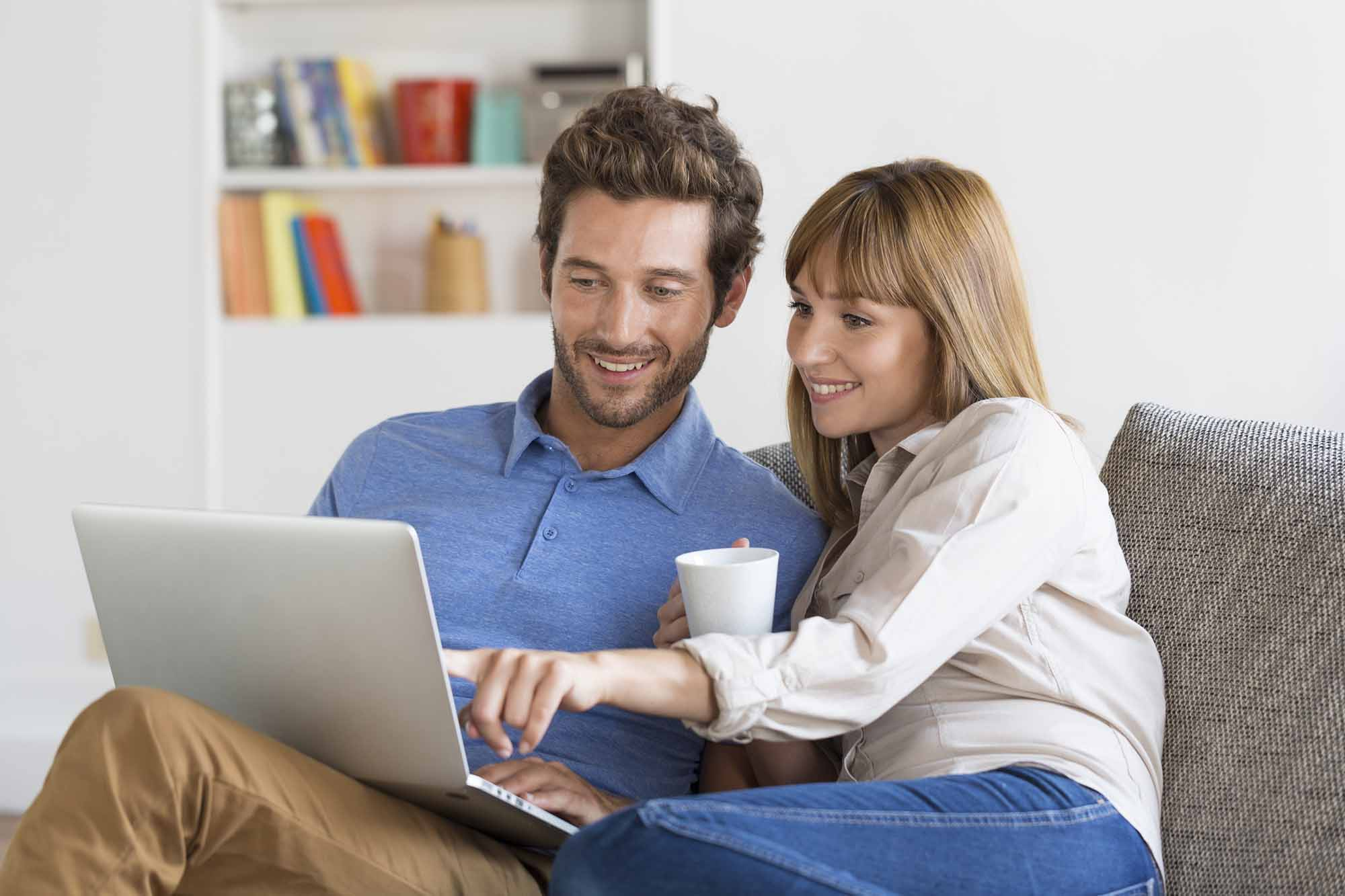 Mid adult man and woman online computer Modern white apartment in background