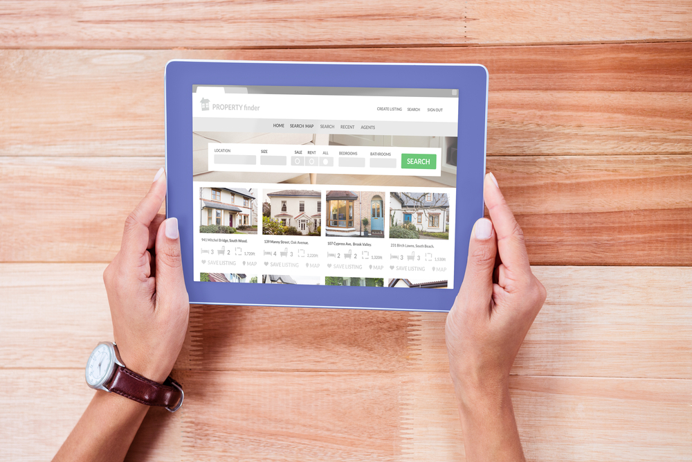 Composite image of property web page against overhead of feminine hands using tablet